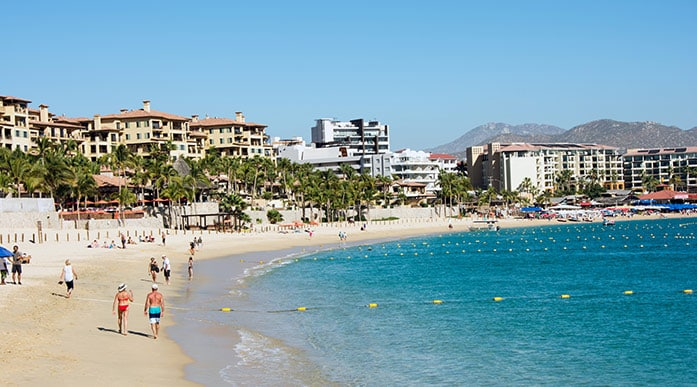 people walking along the beach in playa el medano, cabo san lucas