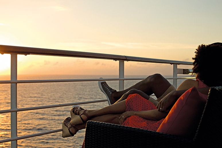 couple staring at the sunset on a cruise