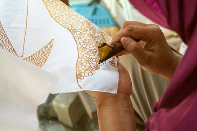 woman adding batik designs on a piece of white fabric