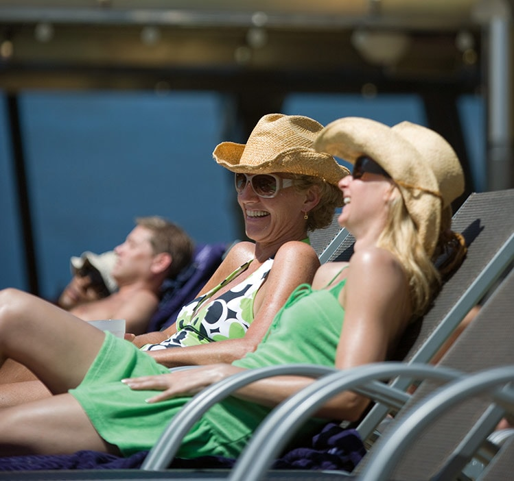 two women wearing green sunbathing on a cruise