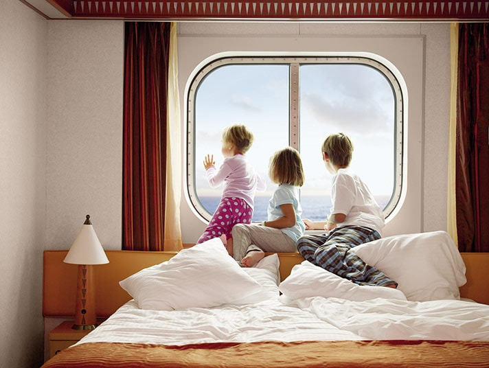 3 kids looking out the window of a stateroom