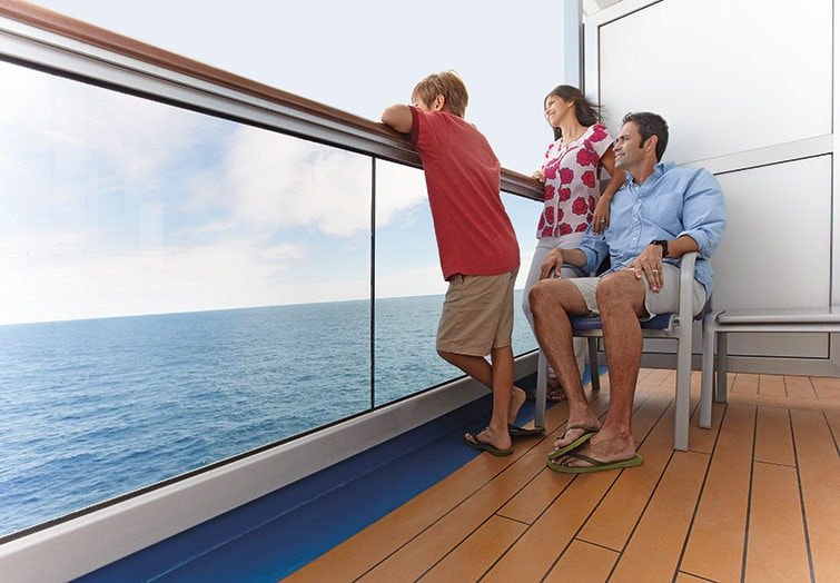 parents on the cruise balcony with their son, looking out at the sea