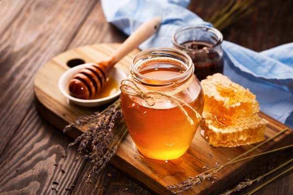golden honey in a glass jar next to a honey dipper and honeycombs