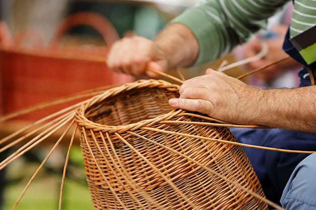 man making handwoven baskets from straw