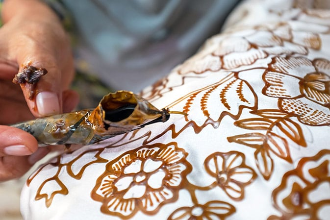 artist creating batiks from a white cloth