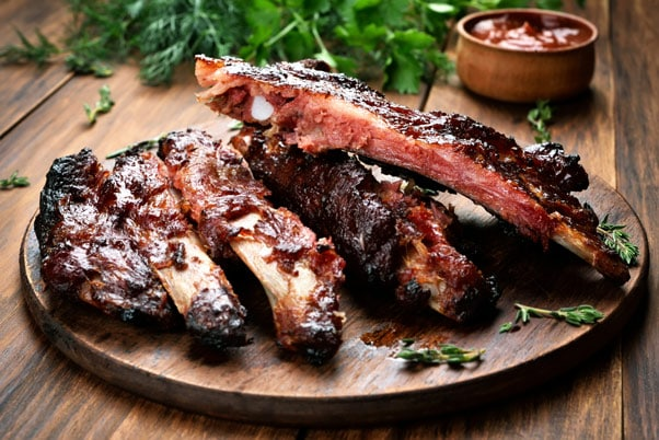 st maarten spare ribs served on wood plate with specialty bbq sauce