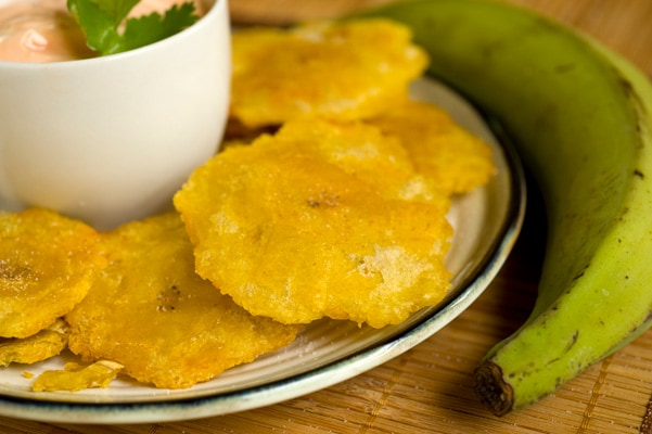 tostones served with pink sauce, next to a plantain