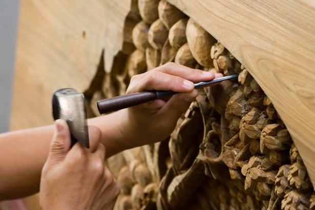 hand carving wood structure using chisel and hammer