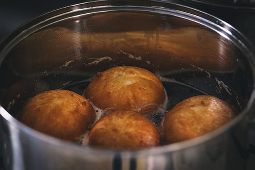 4 johnny cakes being fried in a pot in tortola