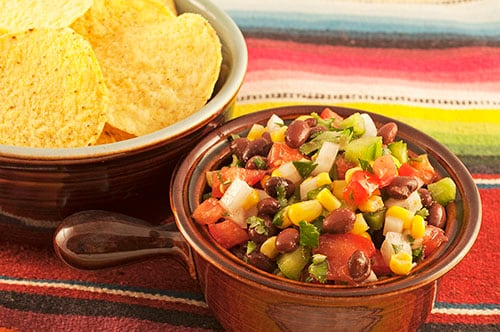 chifrijo, made with beans, rice, and pork, served in a pot with tortilla chips