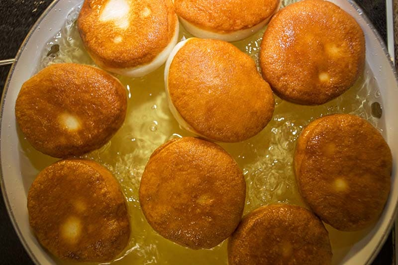 pancake-styled doughnuts called bake being fried in a pot