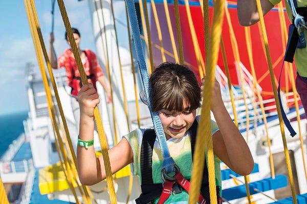 little girl crossing ropes course on carnival sunrise as mom watches