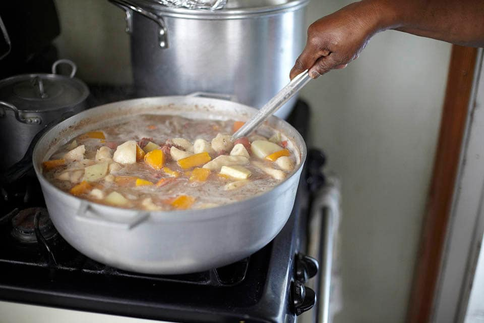 large pot of bouyon soup with sweet potatoes pork and carrots