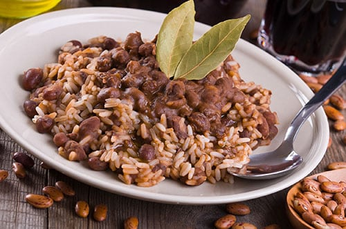 a plate of white rice and pinto beans mixed together with 2 leaves on top