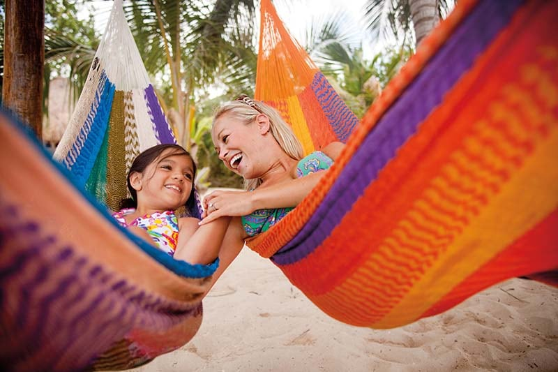mother and daughter relaxing on hammocks in the bahamas