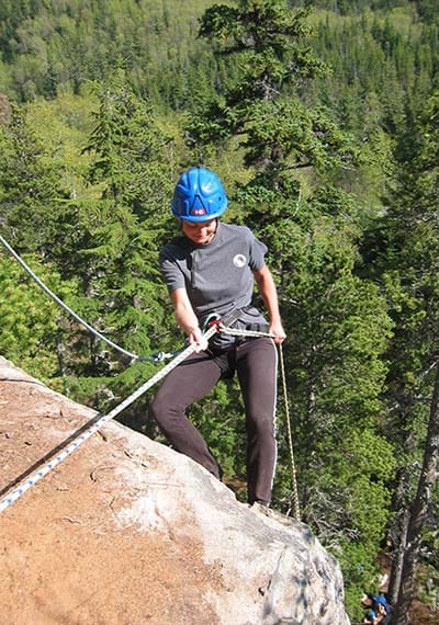 woman rock climbing the klondike rock attached to a rope