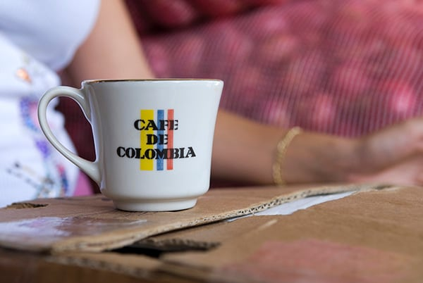 "woman drinking colombian coffee from a mug that says ""café de colombia"""