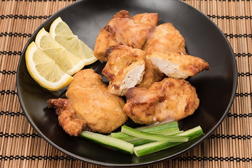 chicharrones de pollo served with lemons on a black plate