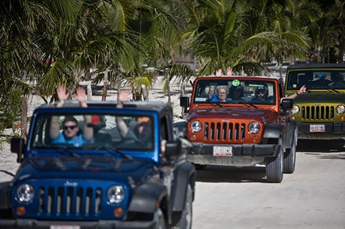 group of people exploring punta sur park in blue, orange, and green jeeps