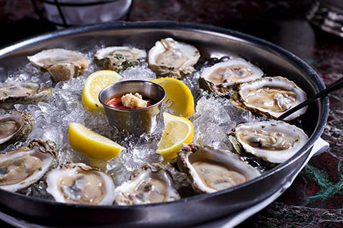 fresh alaskan oysters served on ice with lemons