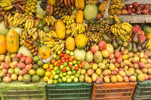 variety of fresh fruits being sold in dominica including bananas, mangos, and papayas