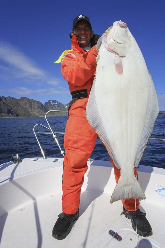man holding a freshly caught halibut from an alaskan excursion