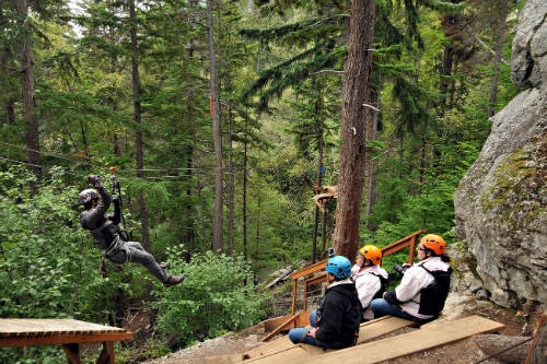 man zip lining between trees in klodike zipline adventure park as friends watch