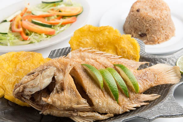 mojarra fish from cartagena served with golden tostones, rice, and salad