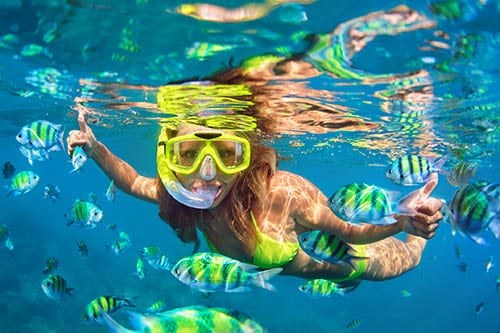 woman snorkeling in Hawaii with fish