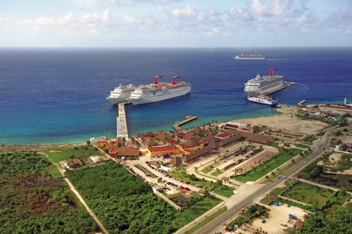 three carnival cruise ships docked in costa maya, mexico as a fourth cruise ship sails to her next adventure