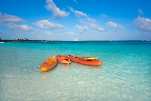 3 orange kayaks with paddles off the shore of costa maya