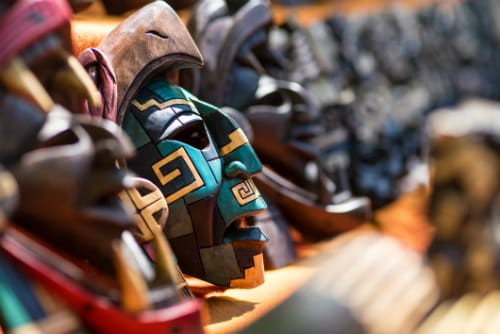 blue and brown wooden mayan mask on a stand with other wooden masks in mexico