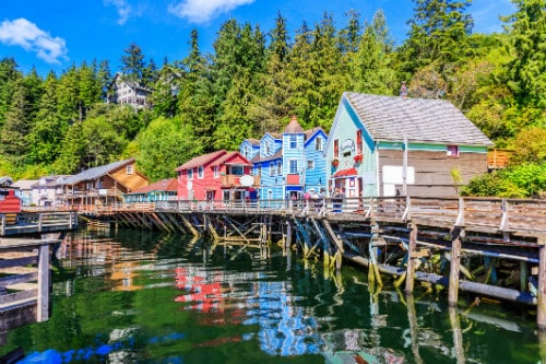 colorful buildings built on a wood foundation along the water in ketchikan alaska