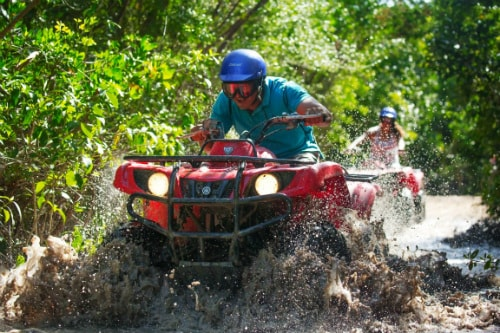 man having fun driving an atv over muddy waters in costa maya