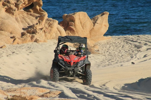 friends driving a red utv along a beach in cabo san lucas