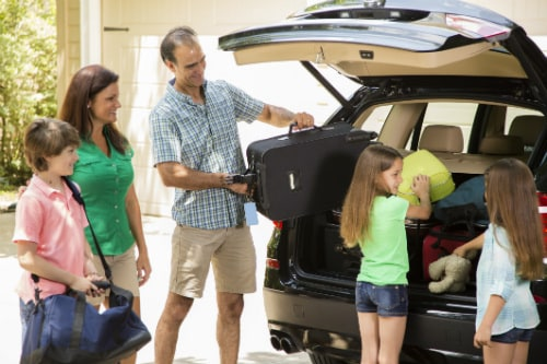 family of 5 putting their suitcases in a black minivan as they prepare to get on a cruise to hawaii