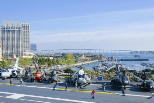 tourist examining different helicopters on an aircraft carrier museum in san diego with coronado bridge in the background