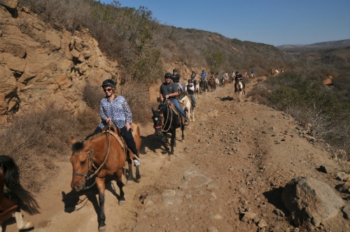 large group of people horseback riding along the scenic trails of san miguel with a guide