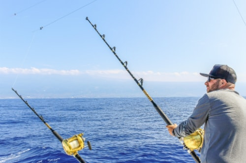 man wearing a black hat and gray shirt deep sea fishing along the coast of ensenada
