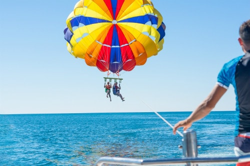 couple parasailing on a yellow and blue parasail off the coast of catalina island