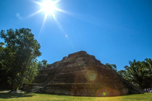 sun shining over a large pyramid in chacchoben mayan ruins