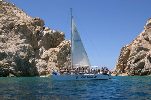 group of people having fun on a white sail boat in cabo san lucas