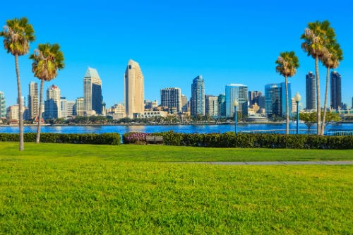 view of the san diego skyline from a park across the water on a sunny afternoon
