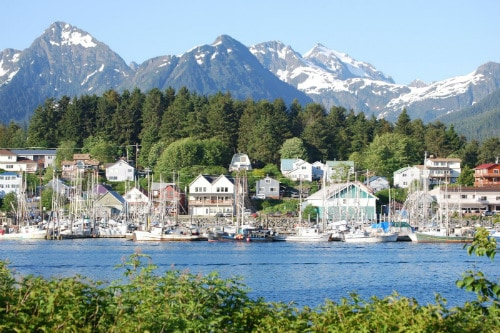 view of the sitka harbor from across the water with snowcapped mountains in the background