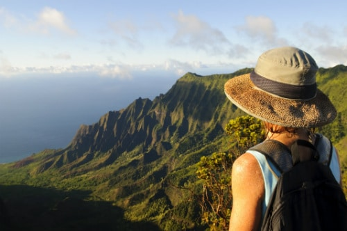 woman wearing a hat an backpack overlooking the waimea canyon in kauai hawaii