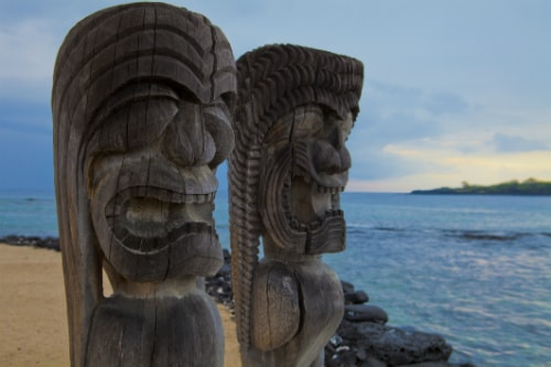 2 hawaiian totem poles looking out towards the pacific ocean