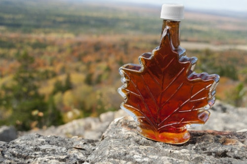 canadian maple syrup in a maple leaf shaped bottle at the edge of a cliff