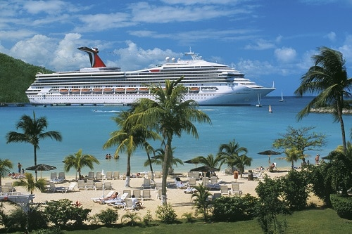 view of a caribbean beach and carnival triumph docked in the background