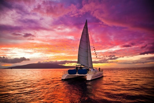 catamaran sailing through the ocean during the sunset near maui