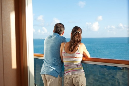 couple enjoying the view of the caribbean sea from their balcony onboard a carnival ship